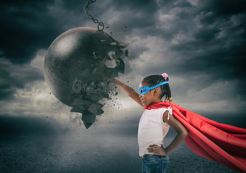 Power and determination of a super hero child against a wrecking ball royalty free stock photography