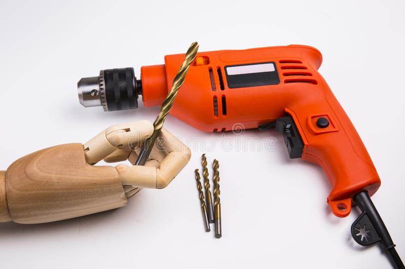 Power Drill. An orange and black power drill. A wooden hand keeps a drill. White background royalty free stock photography