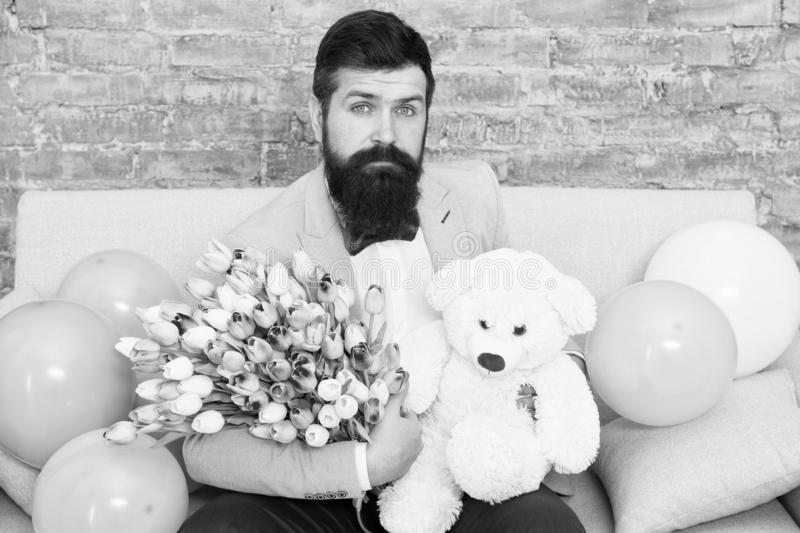 The power of flower. Womens day. Flower for March 8. Bearded man with tulip bouquet. Love you. Present with love. Bearded man hipster with flowers. Love date stock photography