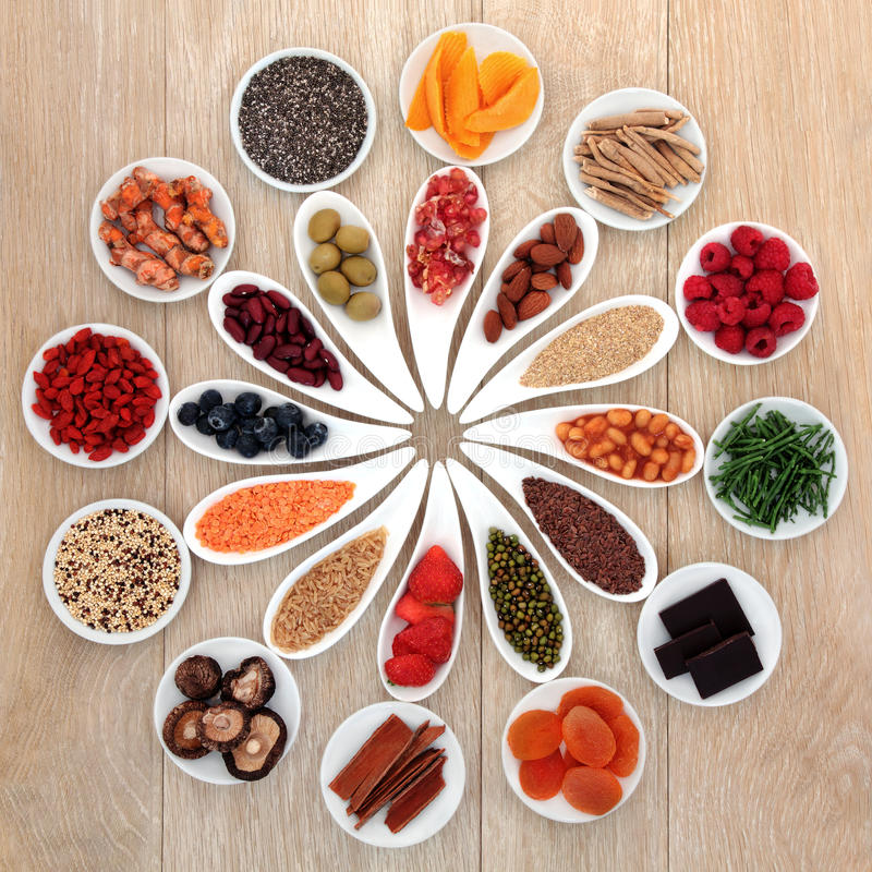Power Food. Healthy super food selection in white porcelain bowls over oak wood background stock images