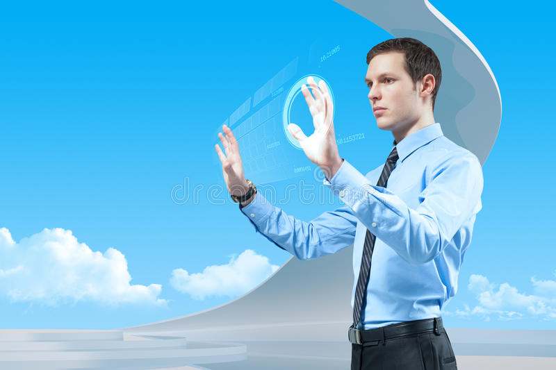 Power of future technologies. Young handsome businessman using futuristic hologram interface and keyboard in the bio style interior stock image