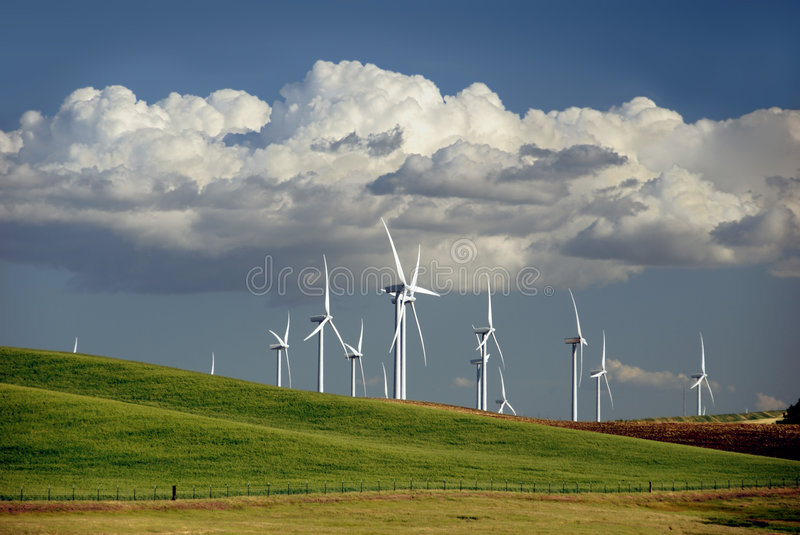 Power Generating Windmills. Stark White Electrical Power Generating Windmills on Rolling Hills, Beneath Dramatic Spring Cumulous Clouds, Rio Vista, California stock image