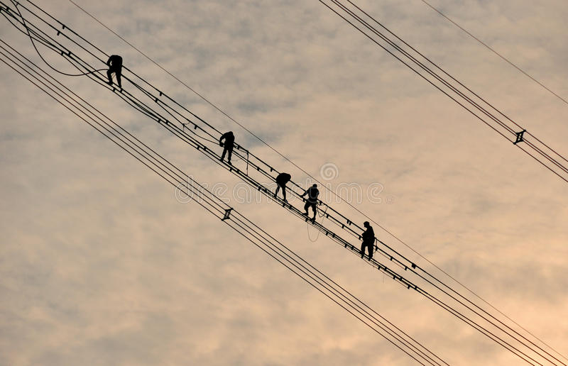 Power grid construction. The work high above the electrician silhouette royalty free stock photography