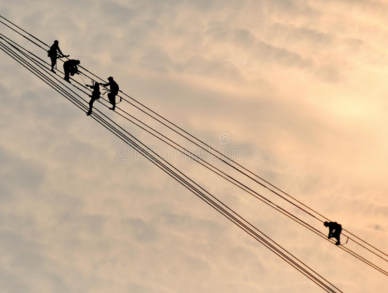 Power grid construction. The work high above the electrician silhouette royalty free stock photo