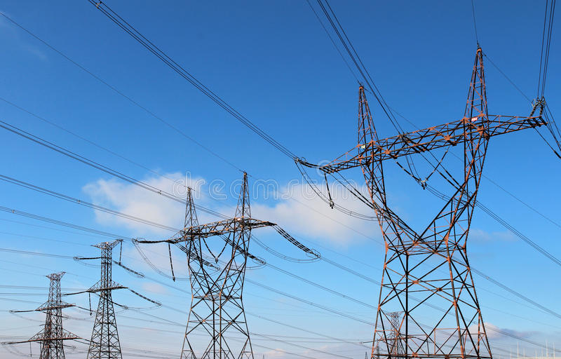 power high voltage tower over blue sky stock images