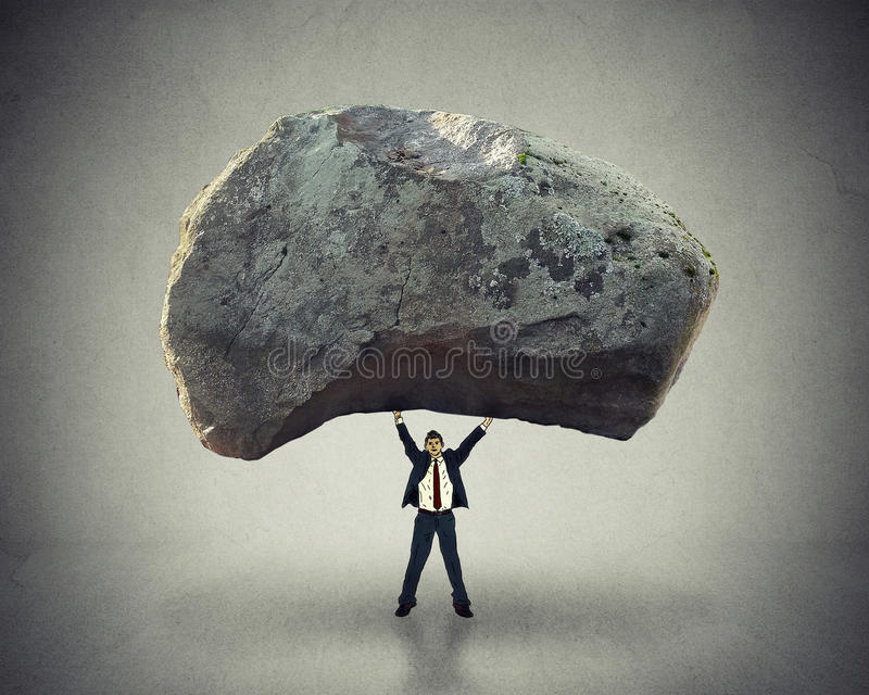 Power leadership ability to inspire man lifting up huge boulder. Power of leadership with the ability to inspire as a businessman lifting up a huge boulder royalty free stock photo