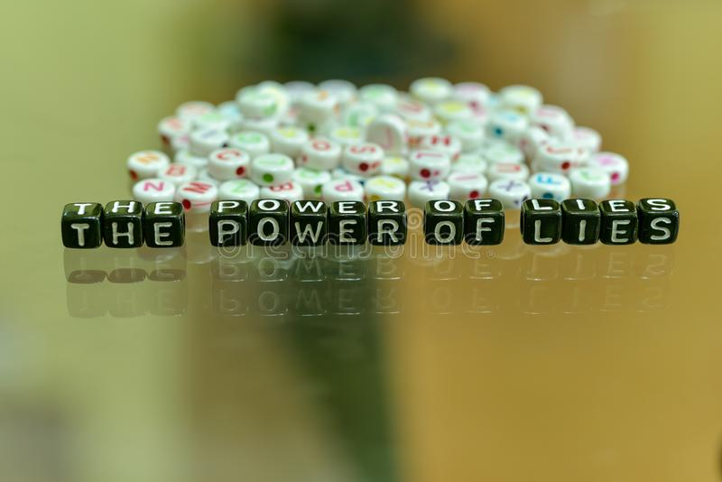THE POWER OF LIES written with Acrylic Black cube with white Alphabet Beads on the Glass Background.  royalty free stock images