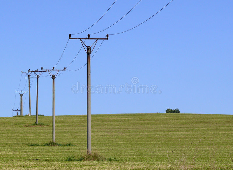 Power line. On field with blue sky stock image