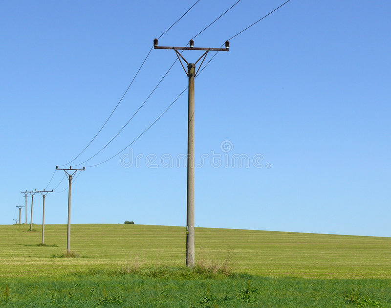 Power line. On field with blue sky royalty free stock photos