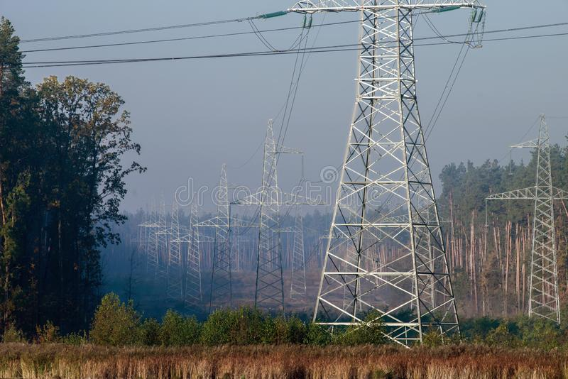 Power line in the cleared area of the forest. Steel electro masts with wires stock photography