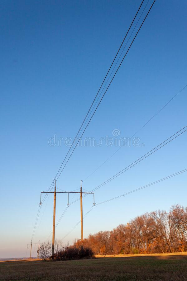 Power line landscape in a field on a clear day royalty free stock photo