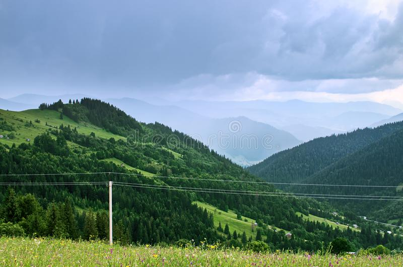 Power line in the mountains. Rainy sky royalty free stock photos