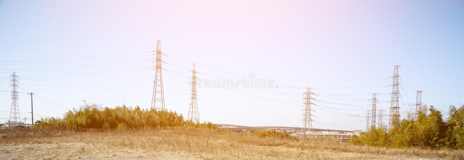 Power line in nature with sun light, wide screen, Technology and nature concept stock photos
