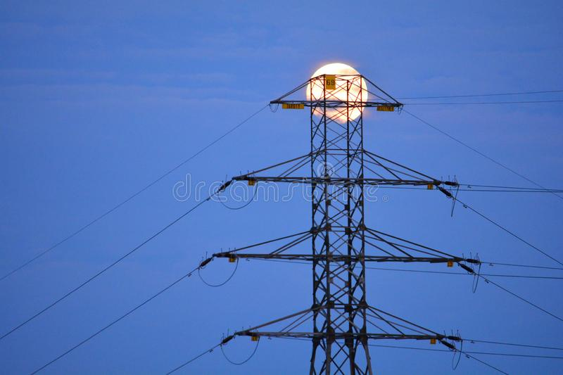 Power line pylon with a full moon in the background stock image