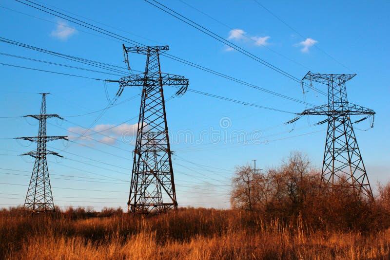 Power line pylons against blue sky background stock photos