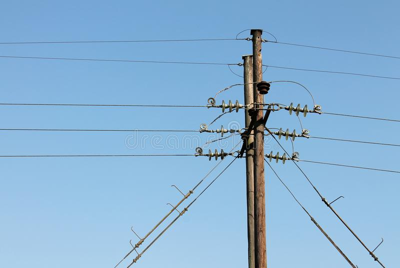 Power line supports against a blue sky background royalty free stock image