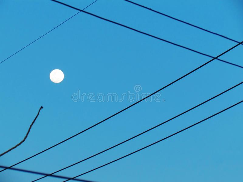 Power line to switch back and forth. It is a graphic pattern. Th. E sky and the full moon in the daytime are the beautiful backdrop. Abstract background royalty free stock images