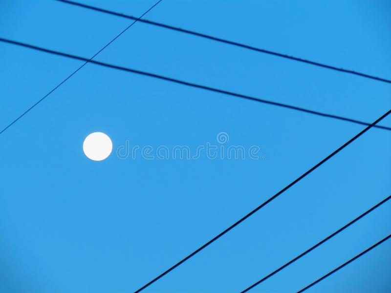 Power line to switch back and forth. It is a graphic pattern. Th. E sky and the full moon in the daytime are the beautiful backdrop. Abstract background stock image