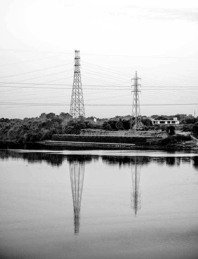 Power line tower at river side. stock photos