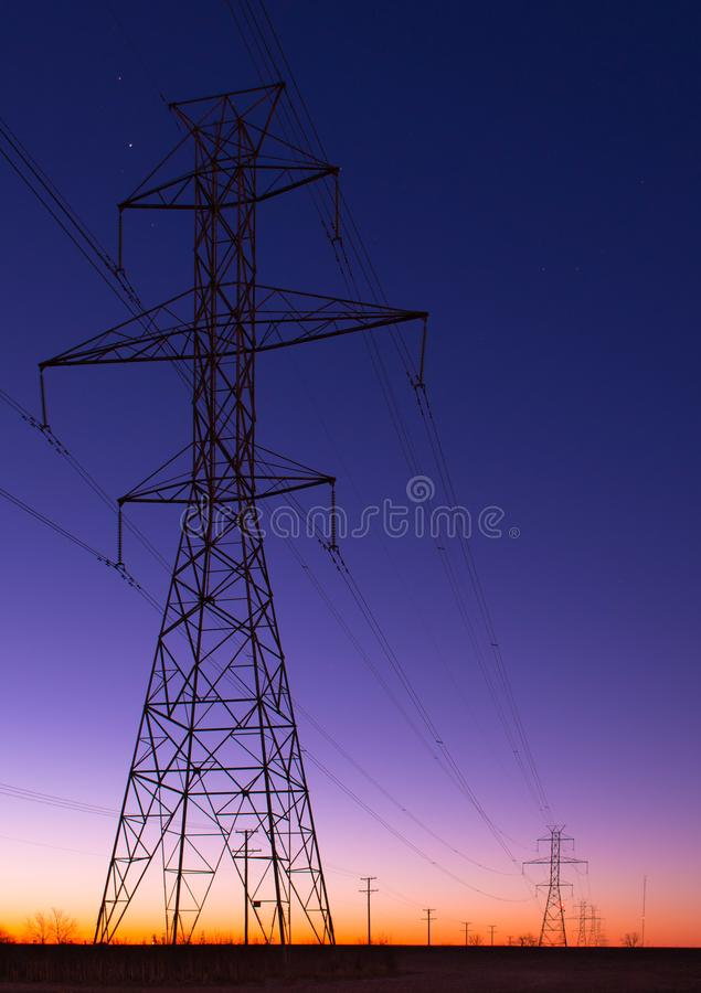 Power line tower row at blue hour stock photography