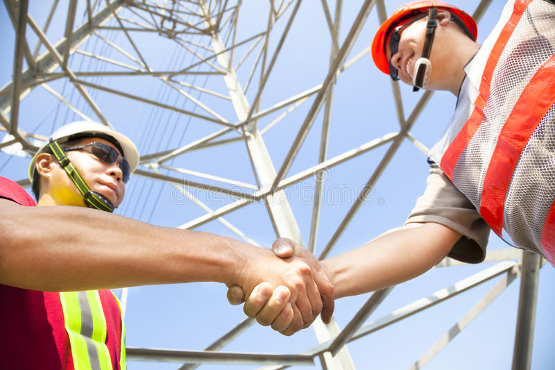 Power line tower workers. Two power line tower workers with handshaking stock photos