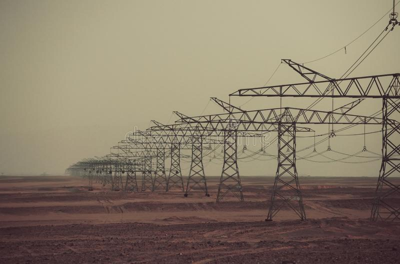 Power line towers in desert on grey sky background stock photography