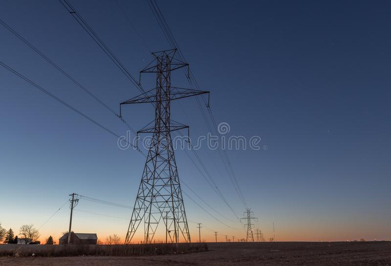 Power line towers on farms royalty free stock photo
