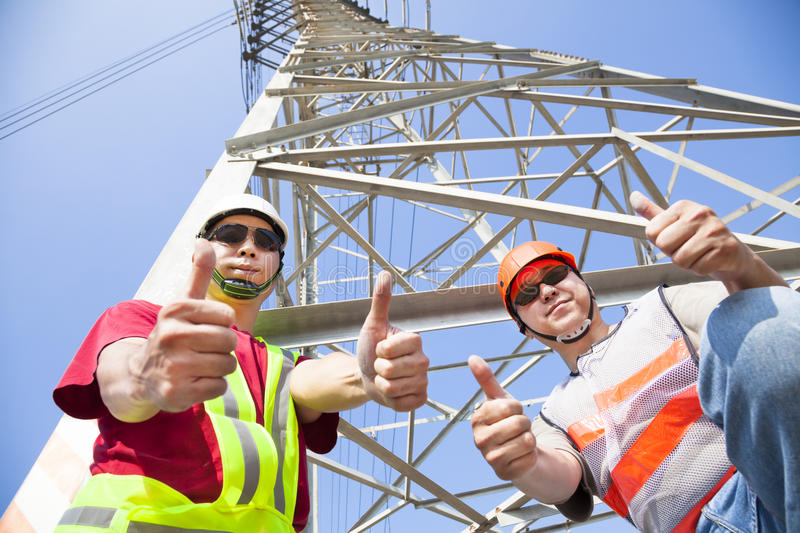 Power line workers with thumbs up. Two power line asian workers with thumbs up royalty free stock photography