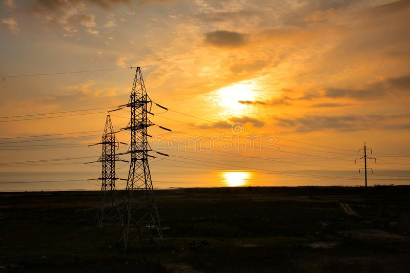 Power lines against rising sun. Power lines on rising sun background stock photo