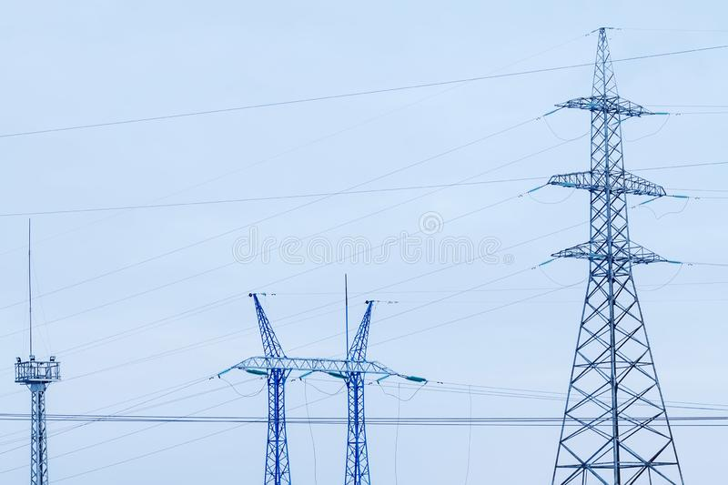 Power lines on background of blue sky close-up. Silhouette of electric pole with copy space. stock image