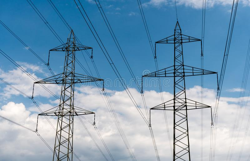 Power lines and pylons in silhouette against a blue sky with white clouds stock image