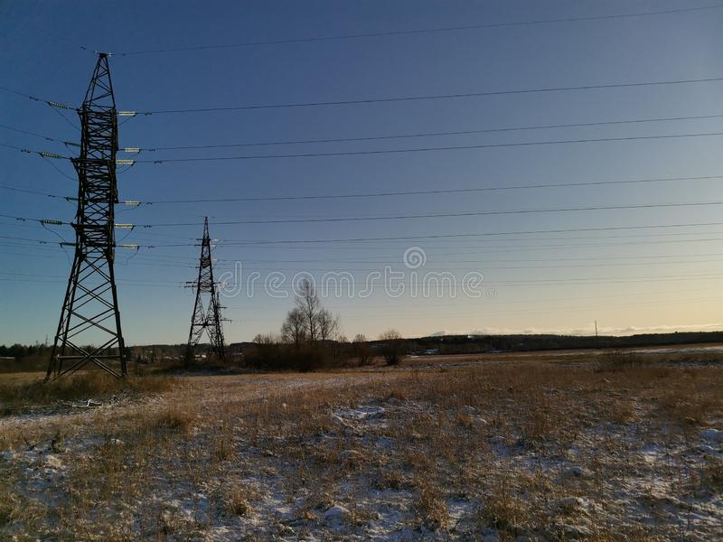 Power lines at sunset. Lep, energy, plant, nature, light, sky, winter, snow, meadow, firld, field, trees stock photo