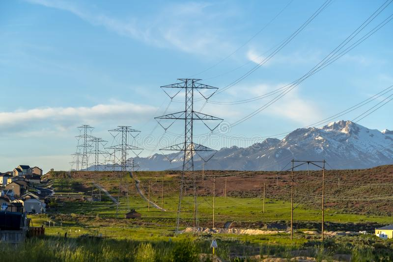 Power lines towering over neighborhood and roads in the valley on a sunny day. Blue sky and mountain with snowy peaks cna be seen in the background stock photo