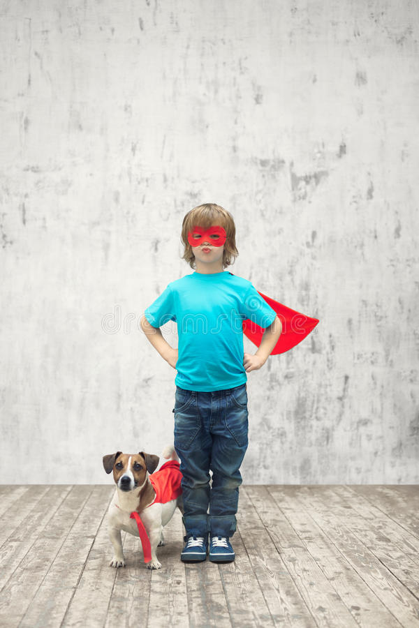 Power. Little superhero with dog indoors royalty free stock image