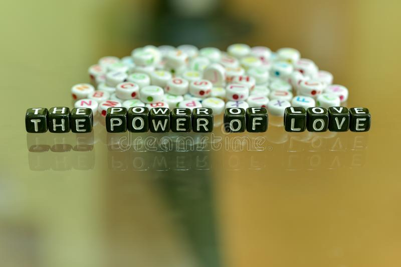 THE POWER OF LOVE written with Acrylic Black cube with white Alphabet Beads on the Glass Background.  royalty free stock photo
