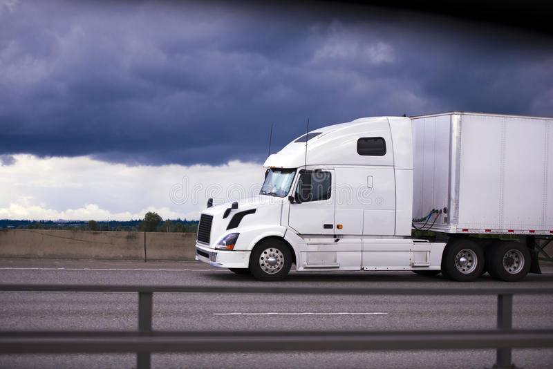 Power modern white rig semi truck trailer side view cab stock images