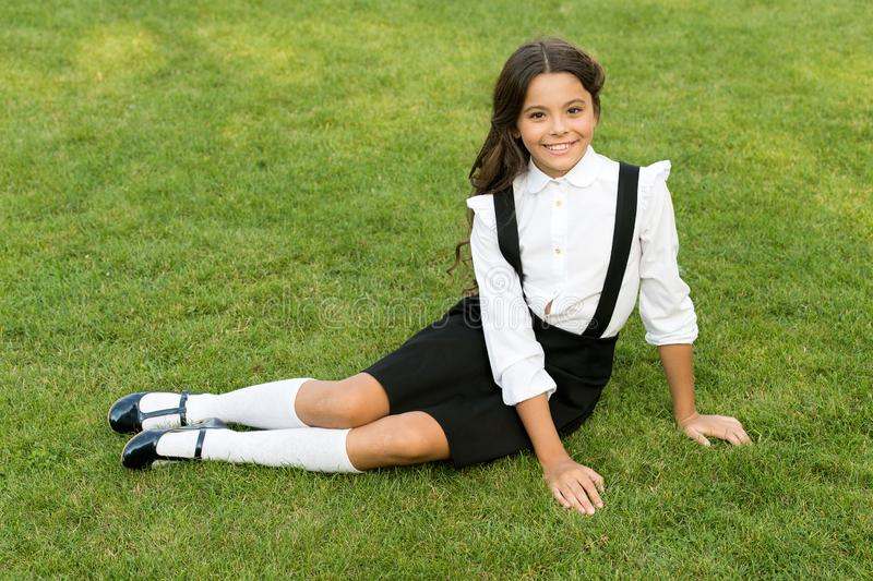 Power in our youth. Smiling pupil sit on grass. Have fun. Happy kid relaxing outdoors. Cheerful schoolgirl. Minute to. Relax. Schoolgirl relaxing. Happy stock images
