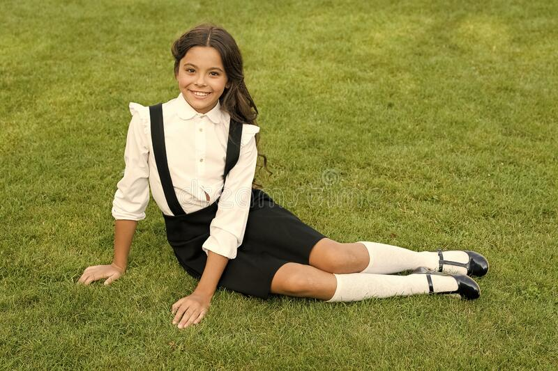 Power in our youth. Smiling pupil sit on grass. Have fun. Happy kid relaxing outdoors. Cheerful schoolgirl. Minute to. Relax. Schoolgirl relaxing. Happy royalty free stock images