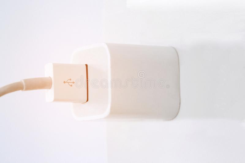 Power outlet with Phone charger in on socket wall, charging.selective focus royalty free stock photo