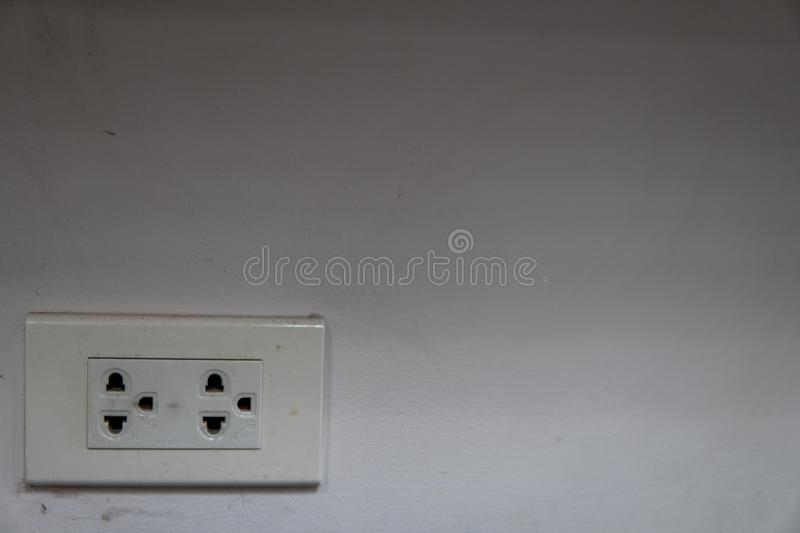 Power outlets with Spider`s wavy on a dirty white wall at one corner of the room stock image