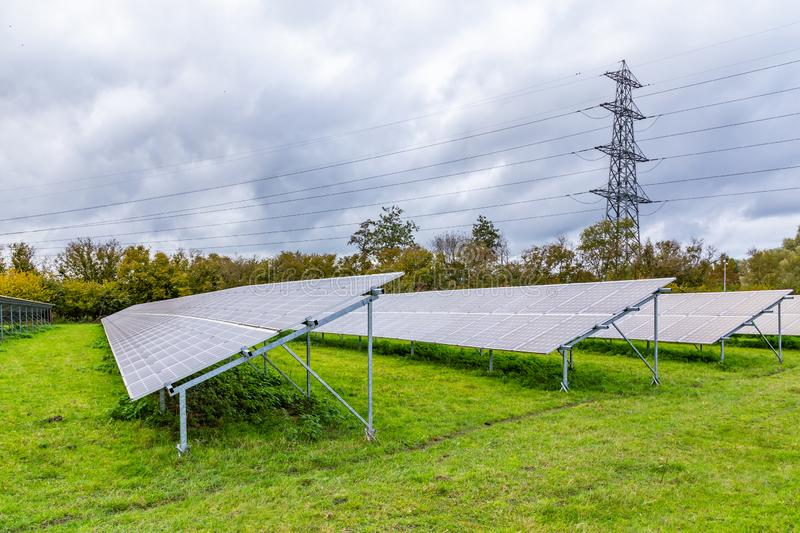 Power panels and post. Modern power solar panels and high voltage post in a Dutch landscape royalty free stock photos