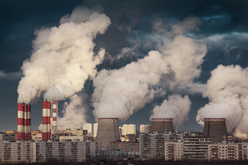 Power plant. Smokestacks emitting smoke over urban cityscape