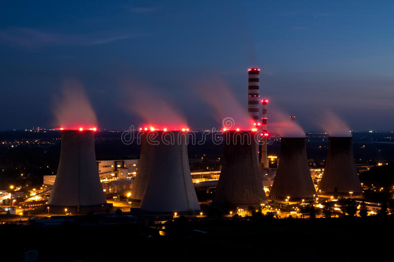 Nuclear Power Plant at night. Night scene with huge nuclear power plant. Smokestacks illuminated with red lamps making blurred effect on smoke stock photo