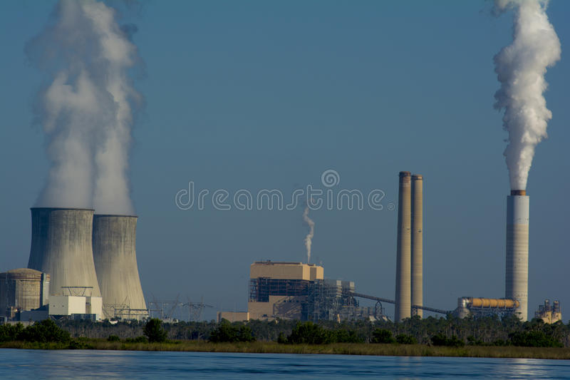 Power plant. Nuclear power plant with two towers and one stack all have stream coming from them royalty free stock photography