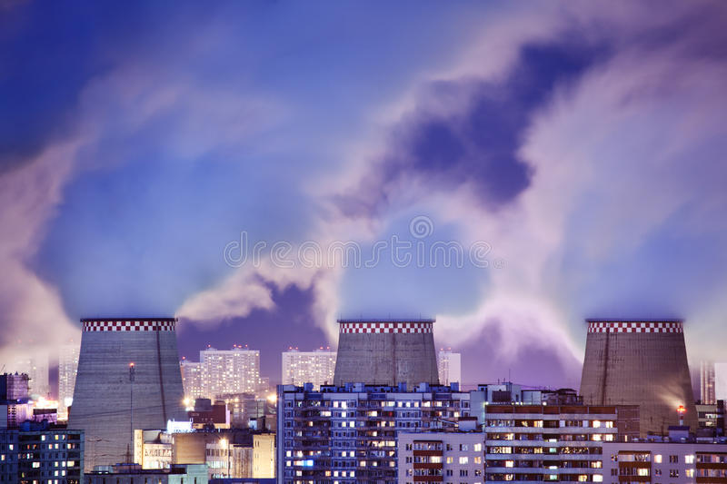 Power plant smoke. Stacks emitting smoke over night cityscape royalty free stock image