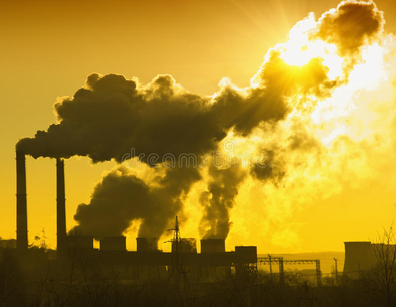 Power plant with smoke. And dirty orange air stock image
