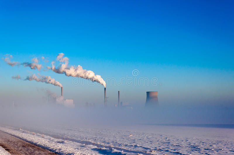 Power plant in a snowy landscape royalty free stock photos