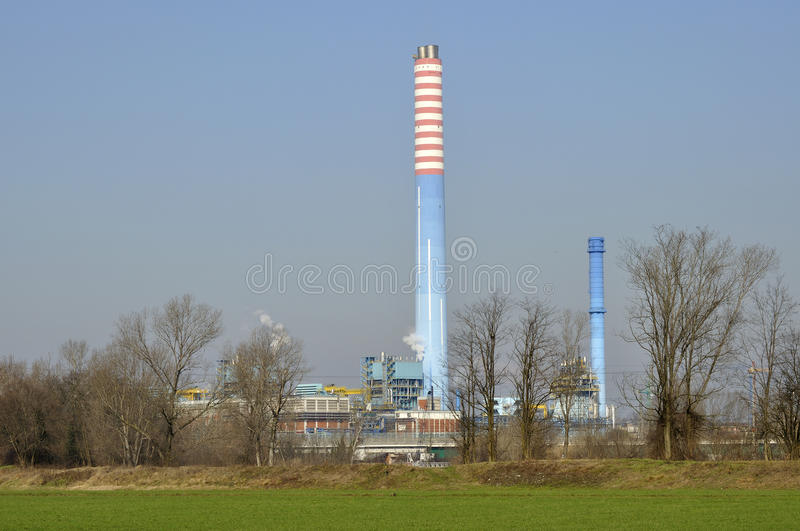 Power plant in winter plains, lombardy. Landscape of winter country with great power plant in the background, shot in bright light royalty free stock photography