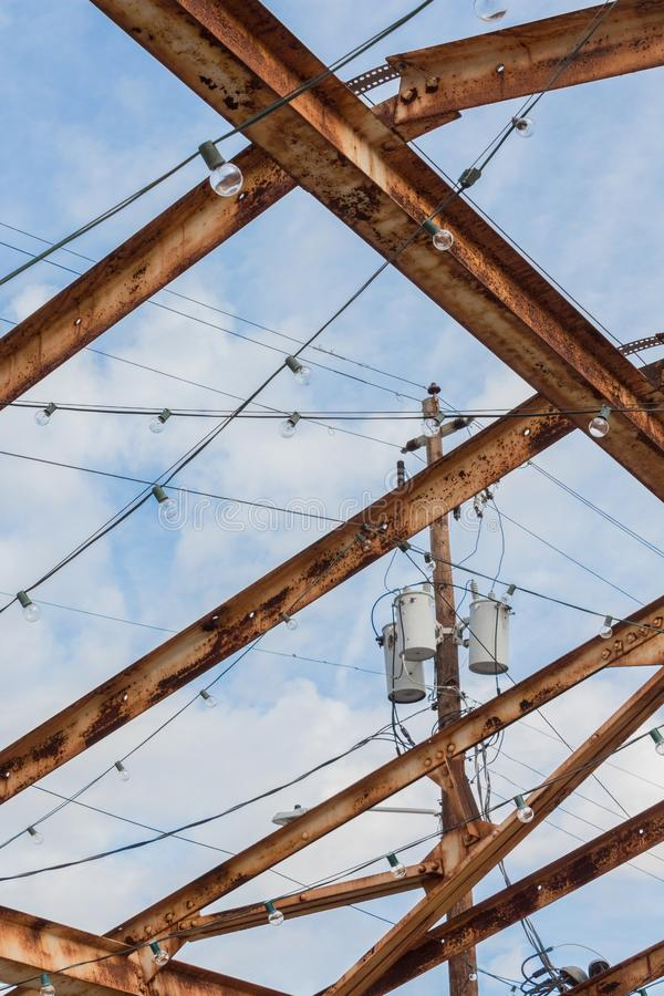 Power pole and transformers set against a blue sky, seen through rusted girder roof system royalty free stock images