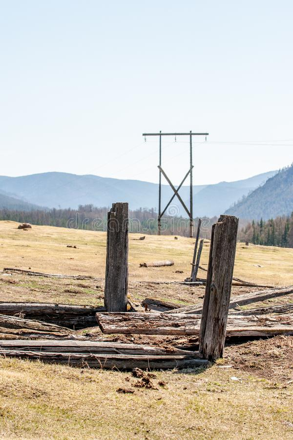 Power poles in the field are visible between two old rotten pillars against the background of hills. The hills are overgrown with forests. Lying old rotten stock photography